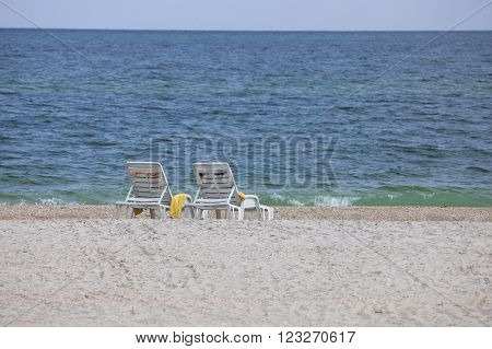 Two white plastic deck chairs on the sandy beach facing the sea with children toys beside