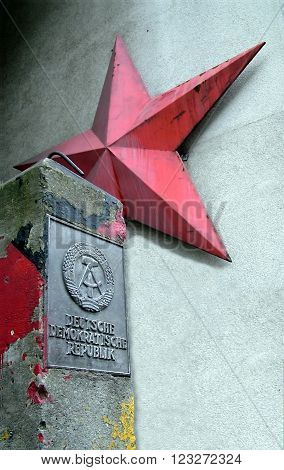 BERLIN, UK - AUGUST 9, 2012: German Democratic Republic sign and red star near Checkpoint Charlie between east and west sectors during the Cold War