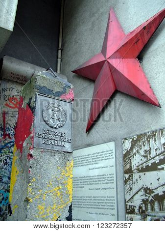 BERLIN - AUGUST 9 2012: German Democratic Republic sign and red star. Column and Berlin wall portion near Checkpoint Charlie between east and west sectors during the Cold War.