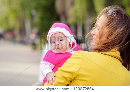 Mom keeps on hand a small child. A family walk in the spring in the Park. The woman in the yellow jacket. The plan. A blurred background.