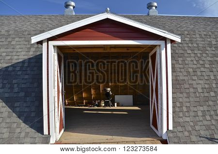ROLLAG, MINNESOTA: SEPT 6, 2015; A drive in gable to a hip-roofed barn exposes an old cream separator at  the (WCSTR) West Central Steam Threshers Reunion grounds  occurs  and 1000s annually attend each Labor Day weekend near Rollag, MN.