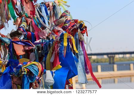 Multi-colored ribbons tied on the tree. Ritual