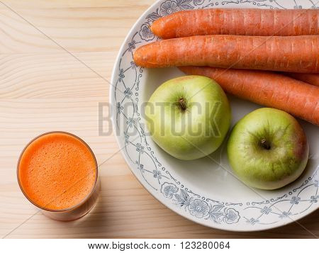 Food. Fruits and vegetables. Two apples some carrots on a plate a glass of fresh juice on wooden background