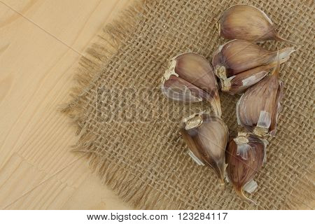 Fresh garlic on a wooden background. Traditional aromatic ingredients in food. Prevention against bad colds and flu.