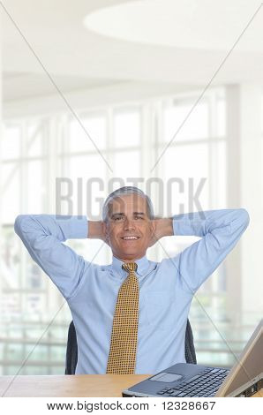 Man At Desk With Hands Behind His Head