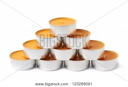 Pyramid of tealight paraffin wax orange candles isolated over the white background