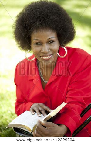 Middle-aged Black Woman Outdoor Reading Bible Smile
