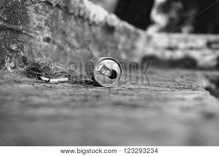 Metal can and cigarette in a park. Lying on the ground. Garbage.