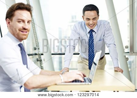 two caucasian business executives working in office looking at camera smiling.