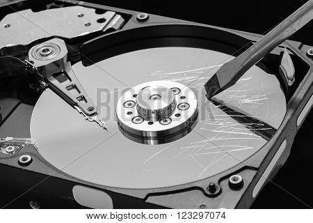 Screwdriver destroying a hard disk drive platter to erase the data