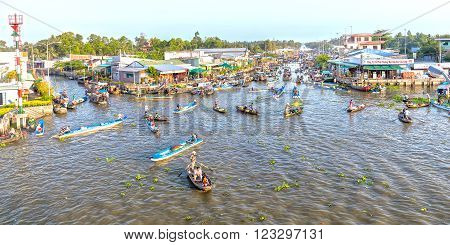 Soc Trang, Vietnam - February 3rd, 2016: Panorama bustling some boats reverse sweep on the morning floating market with hundreds boatload of flowers, agricultural products and vegetables as festival trafficking in Soc Trang, Vietnam