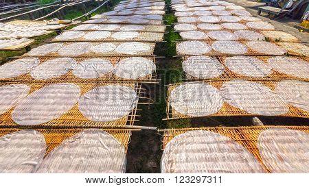 Cake noodles drying on the field with the round cake noodles drying on bamboo blisters dry just put a lot of goods to then cut into strands and bring in food processing areas most delicious noodles Can Tho, Vietnam