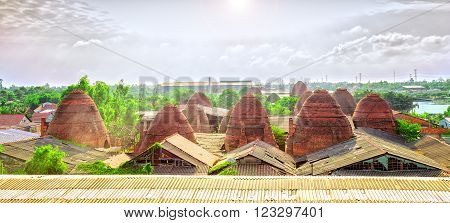 Brickyard village panoramic view from above with dozens of brick kiln rise as a giant mushroom in the sky beautiful sunny morning, this is very constructive effort of workers in craft villages in Vinh Long, Vietnam
