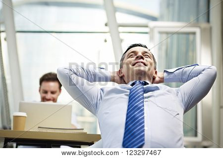 caucasian business person sitting in office thinking daydreaming hands behind head.