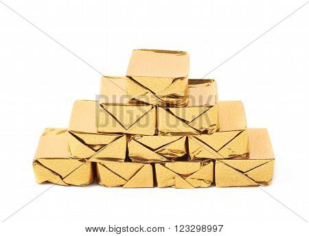 Pile of multiple bouillon stock broth cubes wrapped in golden foil, composition isolated over the white background