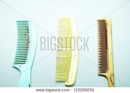 Old dirty and broken colorful combs with hair on gray background.