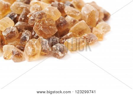 Pile of brown rock sugar crystals isolated over the white background ** Note: Shallow depth of field