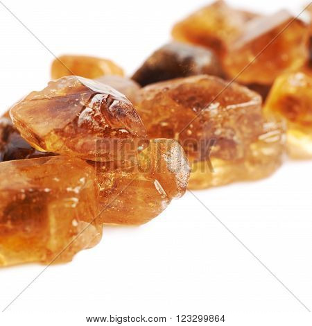 Pile of brown rock sugar crystals isolated over the white background, close-up crop fragment as a copyspace backdrop composition