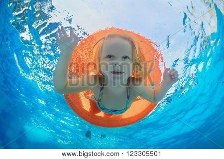 Funny underwater photo of baby girl swimming with fun on orange tube and diving in clear aqua park pool. Healthy family lifestyle and children water sports activity with parents on summer vacation.