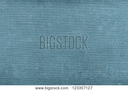 rough texture of old material from cotton or from a sackcloth for a textile background or for wallpaper of blue green color with attritions