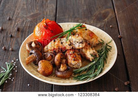 Shish kebab with baked tomato and mushrooms. Spicy shish kebab on wooden table. Homemade supper with fresh vegetables.