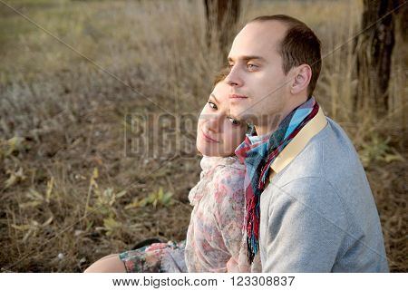 Guy and girl in woods in autumn. Enamored couple sitting side by side on grass and looking away