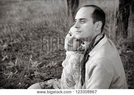 Guy and girl in woods in autumn. Enamored couple sitting side by side on grass and looking away. Monochrome image