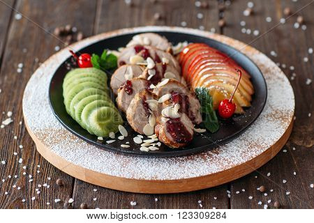 Delicious baked veal with fresh fruits and sweet raspberry  sauce. Baked meat with tropical fruits. Creative food from  baked veal on wooden table.