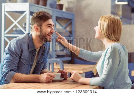 Have some fun. Positive jubilant romantic couple sitting in the cafe at the table and drinking coffee while expressing joy