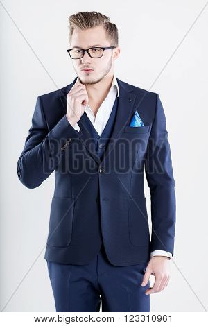 Stylish handsome. Confident young businessman adjusting his eyewear and looking at camera while standing against white background