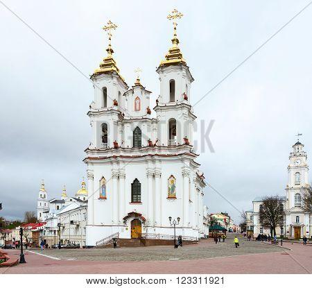 VITEBSK BELARUS - APRIL 16 2015: Unidentified people are walking on the street Suvorov near Resurrection (Rynkovaya) church and town hall Vitebsk Belarus