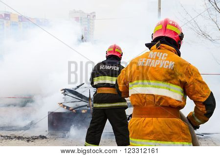 GOMEL BELARUS - MARCH 12 2016: Employees of Emergency Ministry extinguish the remnants of Shrovetide scarecrow after his ritual burning