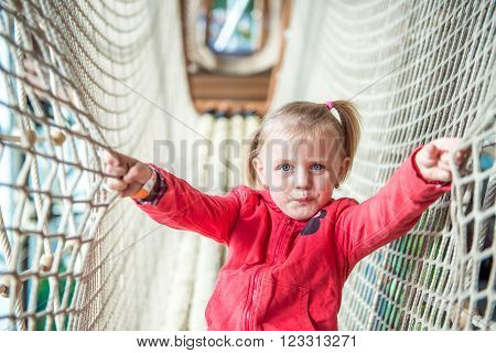 Little cute girl in amusement park rope tunnel