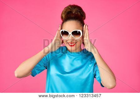 portrait of young beautiful woman in blue silk dress and white sunglasses ot the pink background