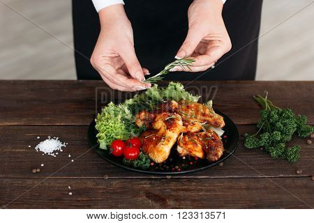 Food decoration on wooden table. Chief presents grilled spicy chicken. Decorating chicken wings with lettuce and tomatoes cherry.