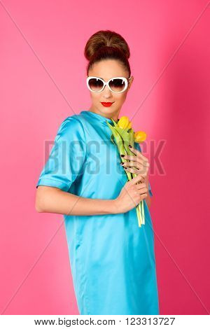 portrait of young beautiful woman in blue silk dress and white sunglasses with yellow tulips ot the pink background