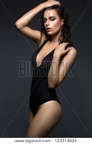 Beautiful wet young woman in black sexy swimwear. Over dark background. Copy space.