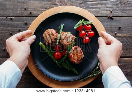 Waiter serving a pork dish. Chief decorating food for retail. Waiter serves food for presentation to the client.