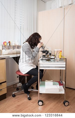 Young cute gynecologist woman working with microscope