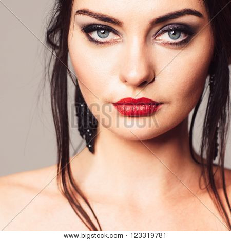 Young attractive woman with bright and bold make-up. Contrast girl with bright and bold make-up. Portrait of contrast brunette.