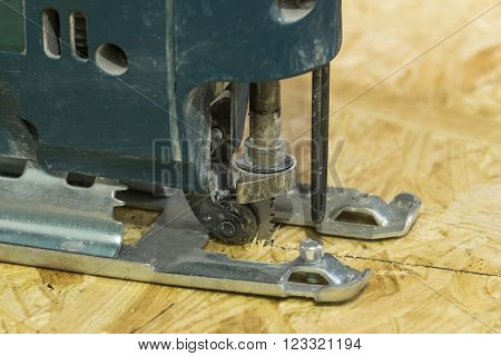 Electricsaw close-up in a working position on the background of OSB