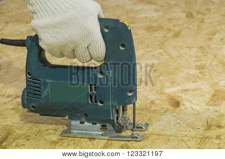 Cutting sheet OSB electric jigsaw. Man directs the hand tool.