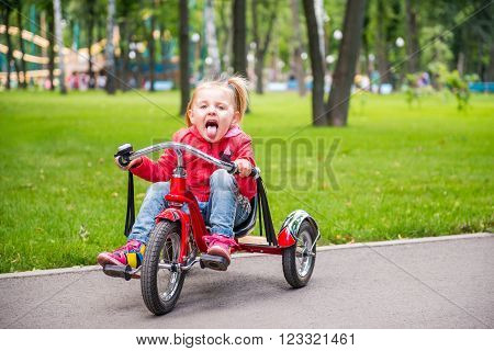 Little girl in amusement park riding on tricycle on the road and showing tongue