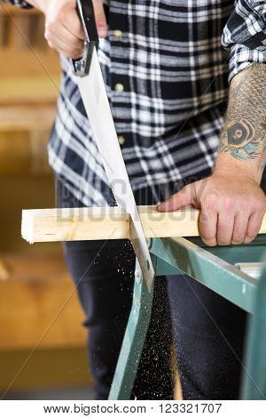 Close-up of a hardworking craftsman sawing with a hand saw in work shop for woodwork.