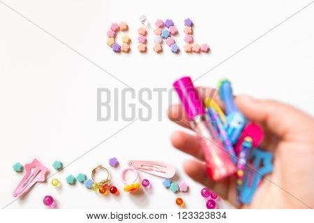 Little girl accessories lifestyle set  on  white background.  Many little girl accessories scattered on blank paper -  pink beads, hair clips, cosmetics. The inscription Girl is on the top of image
