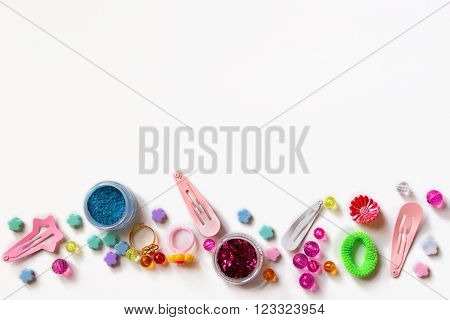 Little girl accessories lifestyle set on white background. Many little girl accessories scattered on blank paper - beads, hair clips, eyeshadow.