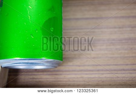 Drink chilled cans green and with water drops attached. There is a wood background, focus water drops.