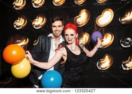 Funky  people clubbing dancing celebrate concept on dance club background. Woman with  colorful balloon and happy man dance on lights background. Concept of night lifestyle.