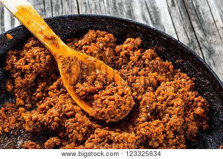 Bolognese ragout in a frying pan authentic recipe wooden background
