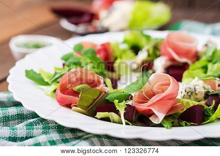 Salad with baked beet, blue cheese, ham and green mix with pesto.